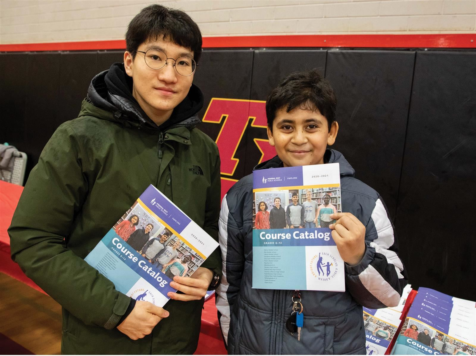 Two Boys holding planning nights catalog